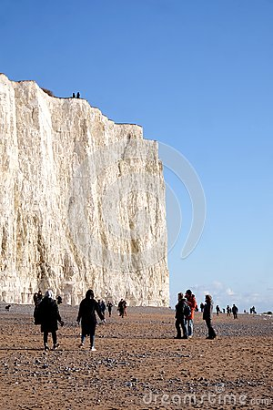 White chalk cliff face with pebble beach and lots of people walk