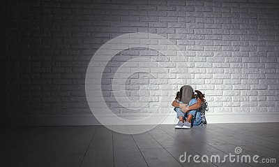 Upset sad sad child girl in stress cries at an empty dark wall