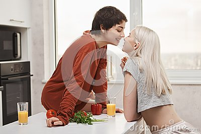 Portrait of stylish and attractive lesbian in red pullover sitting at kitchen table while kissing girlfriend and smiling