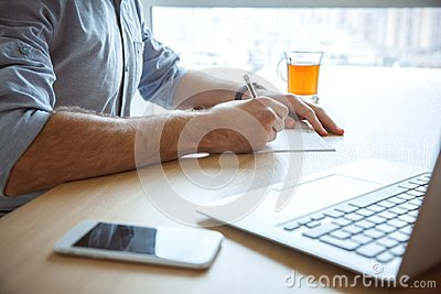 Bachelor man daily routine working from home single lifestyle concept writing close-up