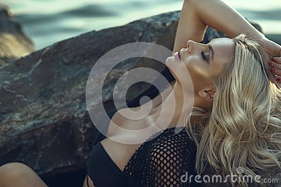 Gorgeous glam tanned blond woman with closed eyes wearing black swimsuit and summer tunic relaxing and bathing in the sun