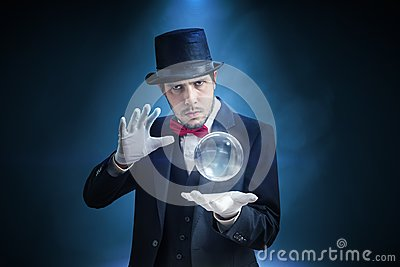 Young illusionist, magician or fortune teller is predicting future with crystal sphere