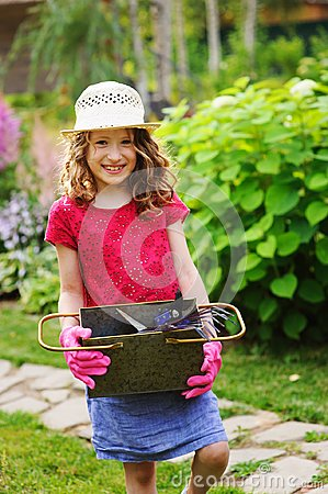 happy child girl playing little gardener and helping in summer garden, wearing hat and gloves