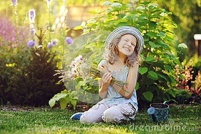 happy child girl playing little gardener in summer, wearing funny hat and holding bouquet of flowers