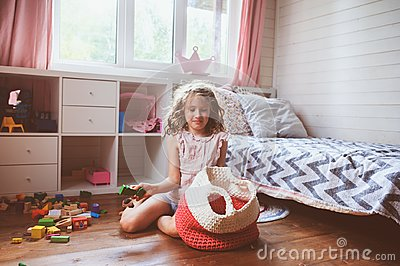 child girl cleaning her room and organize wooden toys into knitted storage bag