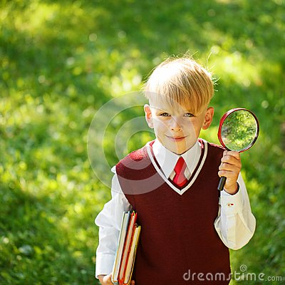 Cute boy going back to school. Child with books and loupe on fir
