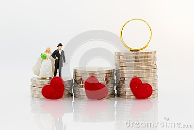 Miniature people : Bride and groom standing on stack of coins with wedding rings. Image use for saving money for marry, accumulate