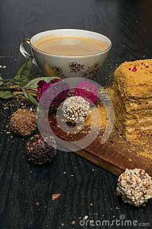 Sweet homemade honey cake and truffeles with coffee in porcelain cup