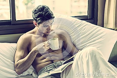 Young man shirtless on his bed with a coffee or tea cup
