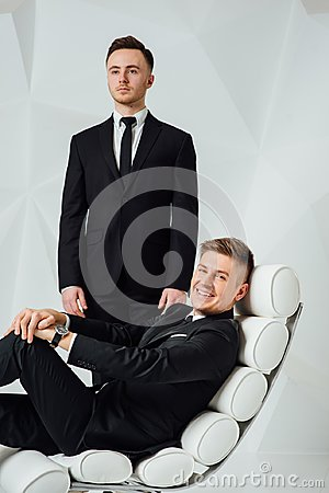 Two young successful guys in black suits