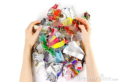 Hands holding a bunch of candy wrappers on a white background. C