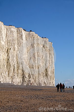 White chalk cliff face with pebble beach and people walking on t