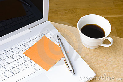 Pen with postit note, laptop and cup of coffee