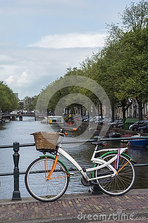 One colourful bike is on the bridge near the canal in Amsterdam