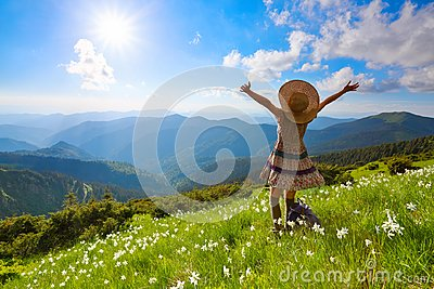 On the lawn in mountains landscapes the hipster girl in dress, stockings and straw hat stays watching the sky with clouds.