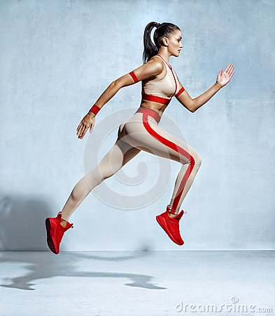 Sporty woman runner in fashionable sportswear on grey background