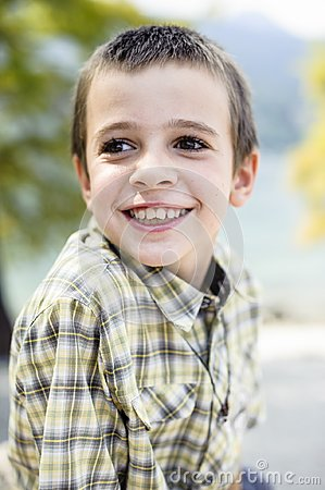 Portrait of 9 year old boy smiling with colorful shirt sitting o