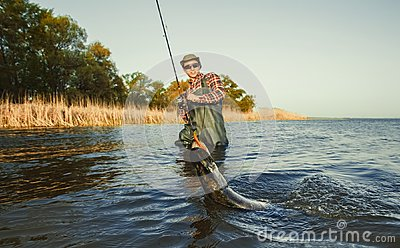 The fisherman is holding a fish pike caught on a hook in