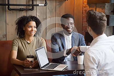 Smiling african-american couple shaking hands to broker advisor
