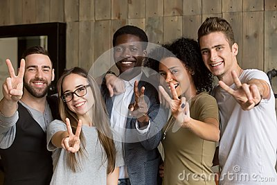 Happy multi-ethnic young people showing peace sign looking at ca
