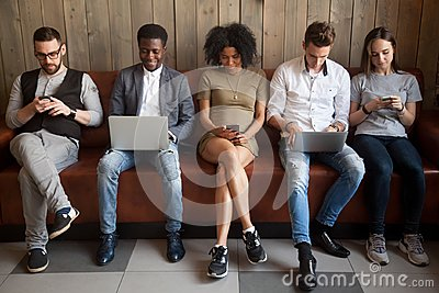 Multicultural young people using laptops and smartphones sitting