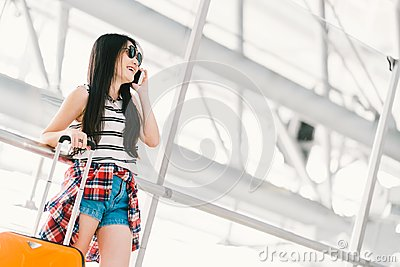 Young Asian traveler woman or college student using mobile phone call at airport with luggage. Study or travel abroad concept