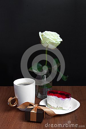 A cup of coffee with a cake and a rose on a black background. Valentine`s Day