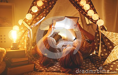 Happy family mother and children reading a book in tent at hom