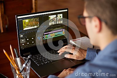 Freelancer video editor works at the laptop computer with movie editing sofware. Videographer vlogger or blogger camera