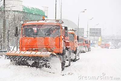 Snowplow trucks removing snow on the road street during blizzard snowstorm in Moscow, Russia.