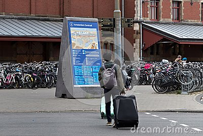 stock image of amsterdam, netherlands - june 25, 2017: tourists with large luggage bags crossing the road in amsterdam.