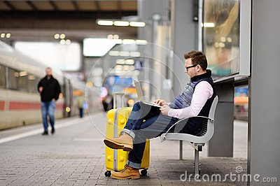 stock image of freelancer working with a laptop in a train station while is waiting for transport
