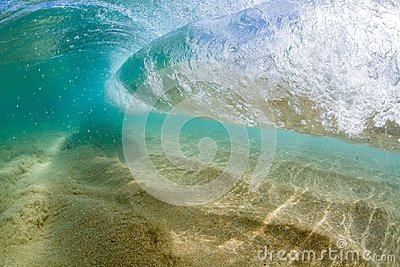 Under water view of Small wave breaking over sandy beach at waimea bay hawaii