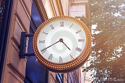 Classic clock on the city street of European city. The clock is set on an old building in the center of Europe.