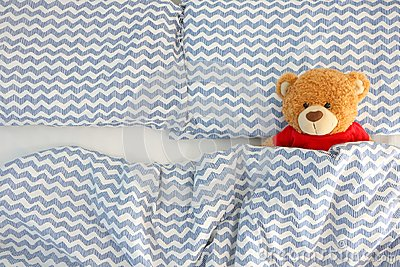 Single brown bear doll wear red shirt sleeping on the bed have space on the left side. Concept waiting for someone to sleep with h