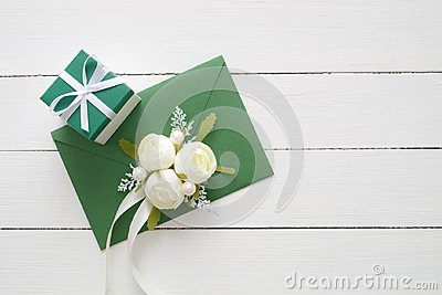 Wedding invitation card or Valentines Day letter in green envelope decorated with white rose flowers and gift box.