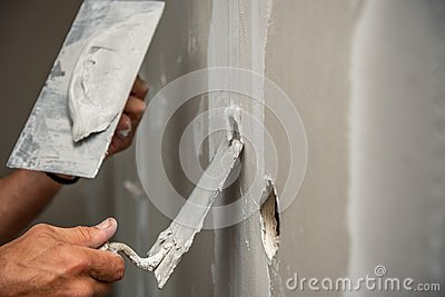 Old manual worker with wall plastering tools renovating house.