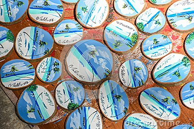 stock image of bunch of wooden souvenirs with landscapes of maldives on it