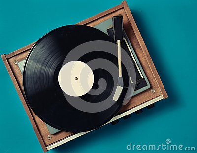 Retro vinyl player on a blue background. Entertainment 70s. Listen to music.