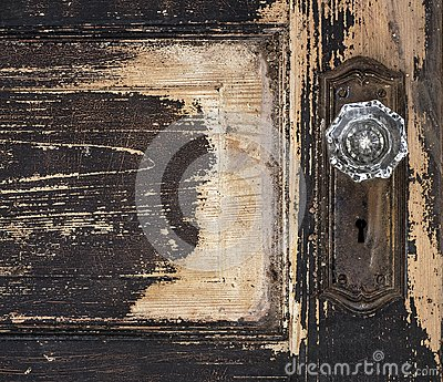 Old weathered antique beat-up wood panel door with chipped peeling paint and glass crystal doorknob and rusty plate