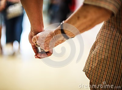 Wrinkled elderly woman`s hand holding to young man`s hand, walking in shopping mall.Family Relation, Health, Help, Support concept