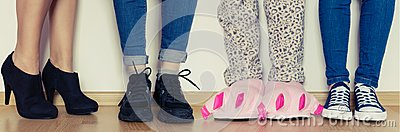 Female legs in slippers and different kind of shoes