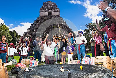 Unidentified Mayan people and tourists surround a fire in Tikal