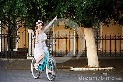 Pretty girl riding blue bike and waving hand.