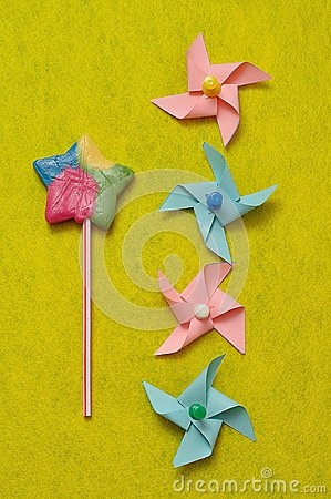 A colorful star shape lollipop with colorful pinwheels on a yellow background