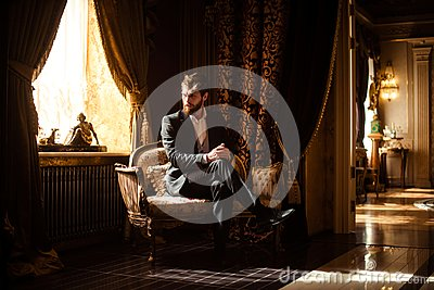 Indoor shot of prosperous intelligent serious businessman sits on comfortable sofa in rich room with luxury furniture