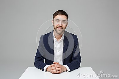 Business Concept - Portrait handsome happy handsome business man in suit smiling and siting in work office. White
