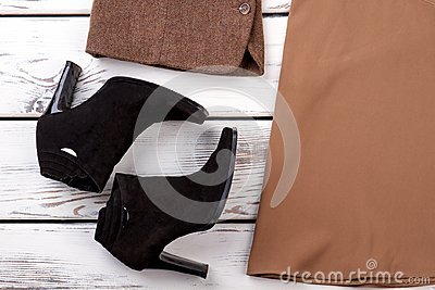 Female high heeled boots on wooden background.