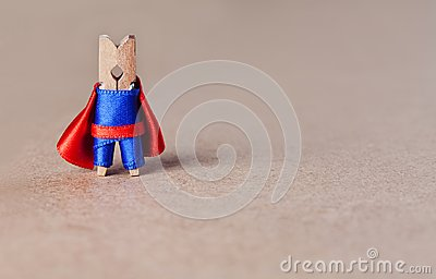 Brave clothespin superhero character on brown craft paper background. blue suit and red cape toy. leadership concept