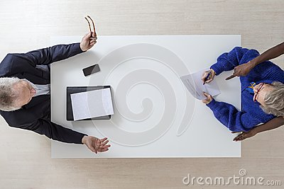 Senior woman signs disposition for his death and will, heritage testament document in a lawyer notary office on white background